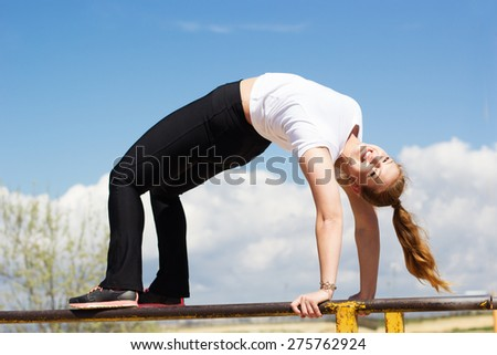 Athletic gymnast girl doing stretching exercise outside near  horizontal bar after running, spring time - stock photo