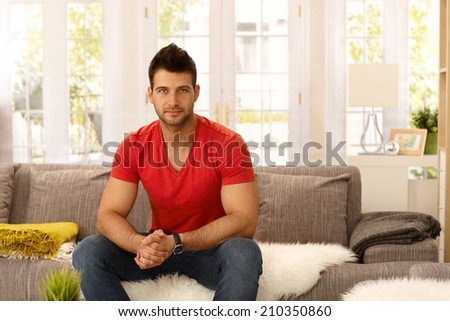 Athletic handsome young man sitting on sofa at home, looking at camera. - stock photo