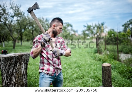 athletic male lumberjack cutting logs for firewood with axe - stock photo
