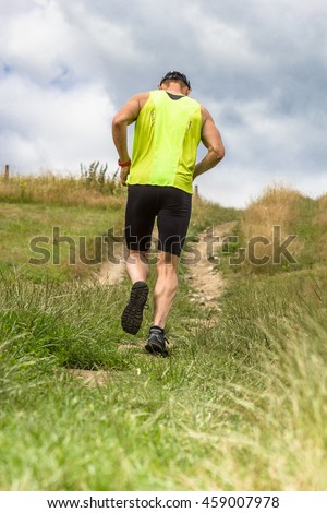 Athletic male runner running uphill on dirt road. Low angle back view.