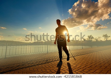Athletic man after jogging in the rays of the evening sun. Sports concept.