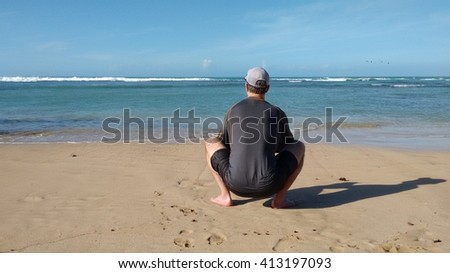 ATHLETIC MAN ALONE ON BEACH LOOKING AT SEA
