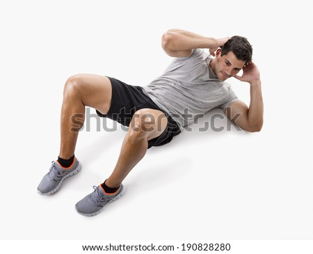 Athletic man doing abdominals, isolated over a white background - stock photo