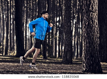 Athletic man doing exercise, running in the forest - stock photo