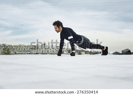 Athletic man doing push ups before going for a run