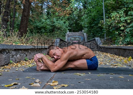 Athletic man doing yoga asanas in the park in the fall