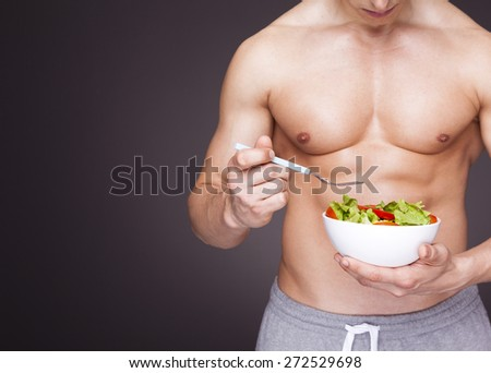 Athletic man holding a bowl of fresh salad on grey background - stock photo