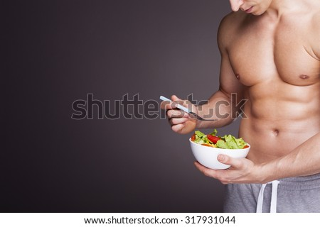 Athletic man holding a bowl of fresh salad on grey background - stock photo