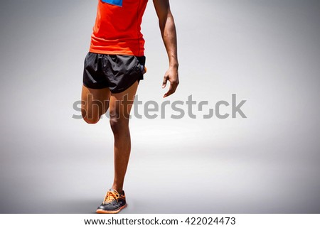 Athletic man hopping against grey background