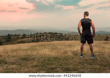 Athletic man in his 30s resting with his hands on his hips while jogging outdoor