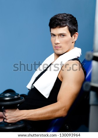 Athletic man in sports wear rests handing a weight in the hand against a set of dumbbells