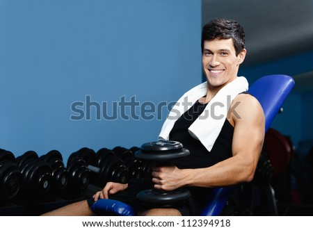 Athletic man in sports wear rests holding a weight in the hand against a set of dumbbells