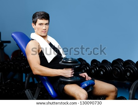 Athletic man in sportswear rests holding a weight in the hand against a set of dumbbells