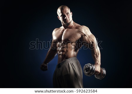 athletic man in training muscles with dumbbell on dark background. Strong bold bodybuilder with six pack, perfect abs, shoulders, biceps, triceps and chest posing.