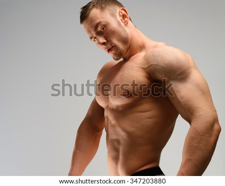 Athletic man posing over grey background and looking at camera.