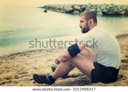 Athletic man resting after strenuous training on the seashore