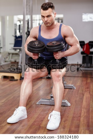 Athletic man resting, preparing before executing shoulder press with dumbbells - stock photo
