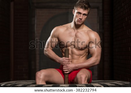 Athletic Man Resting - Workout At Gym With Hammer And Tractor Tire