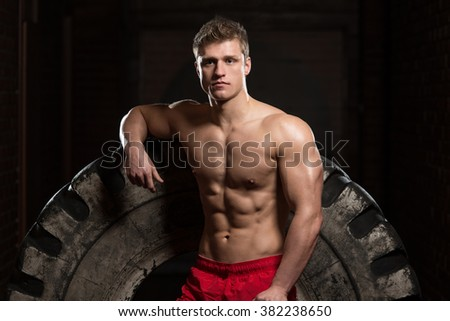 Athletic Man Resting - Workout At Gym With Hammer And Tractor Tire - stock photo
