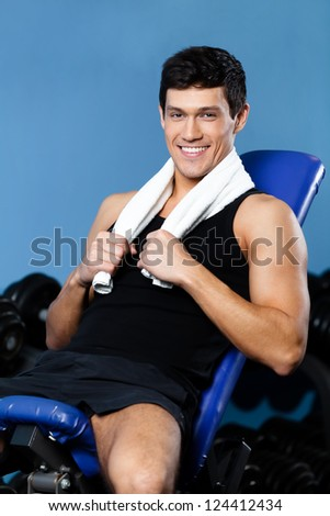 Athletic man rests sitting on blue simulator in training gym - stock photo
