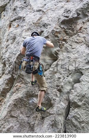 Athletic man rock climbing on a high rock wall - stock photo