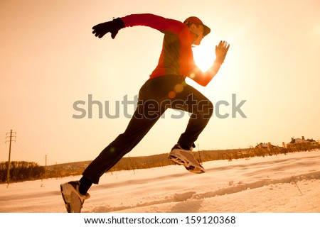 Athletic  man running in winter morning - stock photo