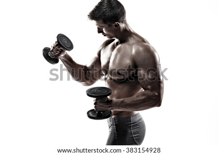 Athletic man showing muscular body and doing exercises with dumbbells - stock photo
