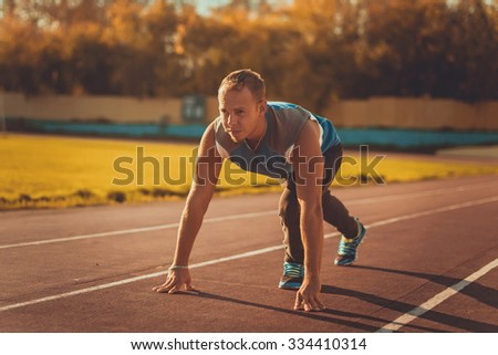 Athletic man standing in a posture ready to run on a treadmill - stock photo