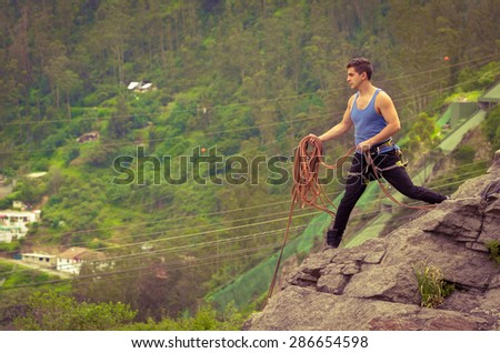 athletic man standing on cliff with rope in hands ready to throw - stock photo