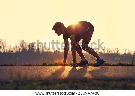 Athletic man starting evening jogging in sun rays - stock photo