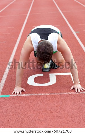 Athletic man waiting in starting block in a stadium