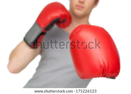 Athletic man wearing red boxing gloves on white background