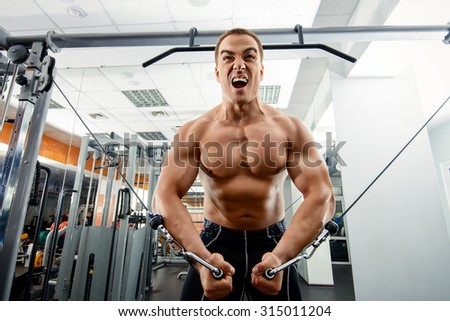 Athletic man working out with weight training equipment in a gym. Sports, bodybuilding. Healthy lifestyle. - stock photo