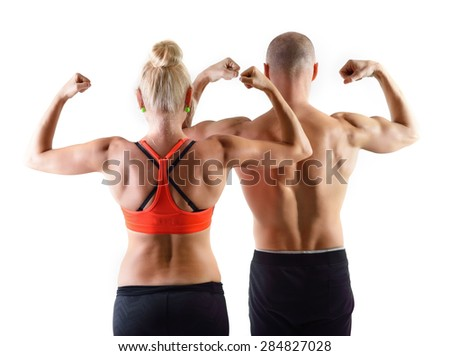 Athletic middle-age man and woman posing in studio. Back view. - stock photo