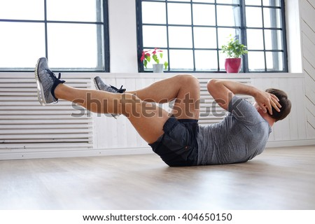 Athletic middle age man doing stomach workouts at home. - stock photo