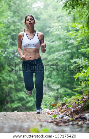 Athletic middle aged caucasian woman on a run in green leaved woods on a dirt road in Surry, Maine, USA during the Summer. - stock photo