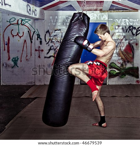 Athletic muay thai boxer giving a forceful knee kick during a training with a boxing bag - stock photo