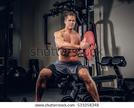 Athletic muscular male warming up with barbell weight in a gym club.
