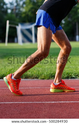 Athletic muscular man legs in motion on running track outdoors