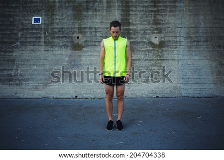 Athletic muscular runner in bright reflective sportswear standing on the background of concrete wall taking break after intensive evening jog, fitness and healthy lifestyle concept - stock photo