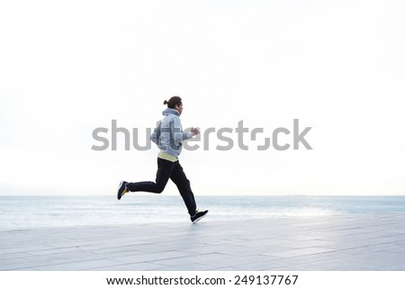 Athletic runner training on morning jog outdoors listening to music on smart phone, young sportive man running along the beach with beautiful sunrise on background