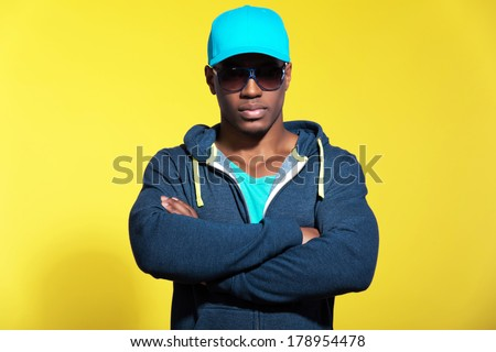 Athletic runner with sunglasses wearing blue sportswear fashion. Black man. Blue cap and sweater. Intense colors. Studio shot against yellow background. - stock photo