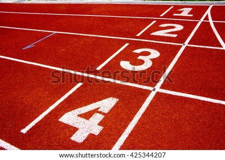 Athletic running track in weathered red rubber with numbered lan
