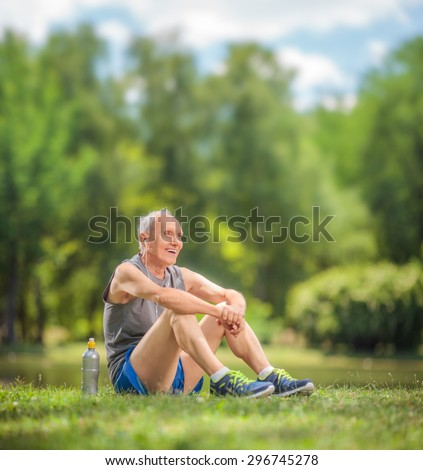 Athletic senior in sportswear sitting on grass in a park and listening to music on headphones shot with tilt and shift lens - stock photo