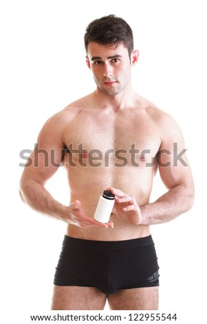 Athletic sexy male body builder holding a boxes with supplements on his biceps - stock photo