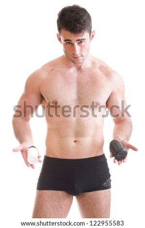 Athletic sexy male body builder holding a boxes with supplements on his biceps, man holding bottle of pills
