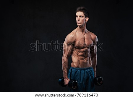 Athletic shirtless male holds dumbbells.