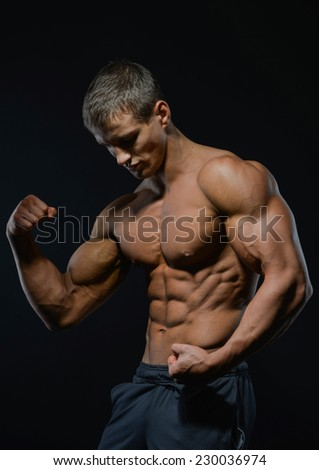 athletic shirtless male model in flexing muscles