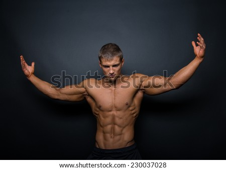 athletic shirtless male model in flexing muscles - stock photo