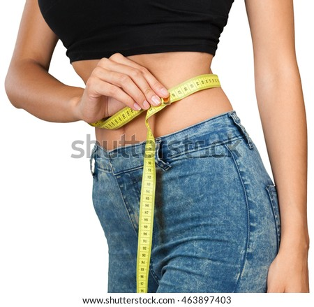 Athletic slim woman measuring her waist by measure tape